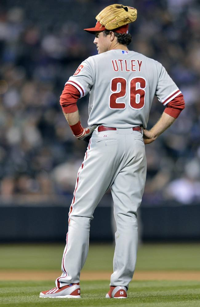 Philadelphia Phillies second baseman Chase Utley wears his glove on his head while waiting for a pitching change against the Colorado Rockies during the seventh inning of a baseball game on Friday, April 18, 2014, in Denver