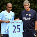Manchester City's new manager Manuel Pellegrini, right, poses for photos with new signing Fernandinho from Brazil, holding his new team's shirt, following a press conference, at Carrington Training Ground, Manchester, England, Wednesday July 10, 2013. (AP Photo/PA, Dave Thompson)
