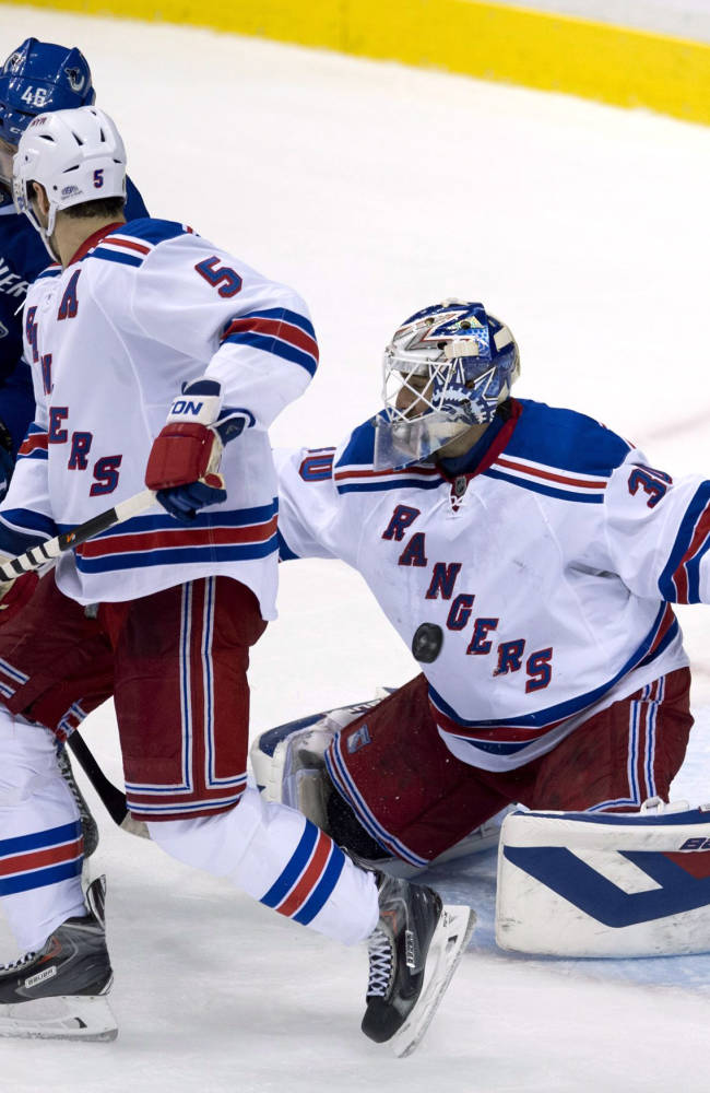 Vancouver Canucks left wing Nicklas Jensen (46) tries to get a shot past New York Rangers goalie Henrik Lundqvist (30) as Rangers defenseman Dan Girardi (5) watches during the second period of an NHL hockey game Tuesday, April 1, 2014, in Vancouver, British Columbia