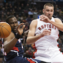 Toronto Raptors forward Jonas Valanciunas, right, battles for the loose ball against Atlanta Hawks forward DeMarre Carroll, left, during the first half of an NBA basketball game in Toronto on Sunday, March 23, 2014 The Associated Press