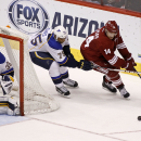Phoenix Coyotes' Jeff Halpern (14) skates with the puck ahead of St Louis Blues' Ryan Reaves (75) as Blues goaltender Ryan Miller (39) positions himself in net during the third period of an NHL hockey game on Sunday, March. 2, 2014, in Glendale, Ariz. The