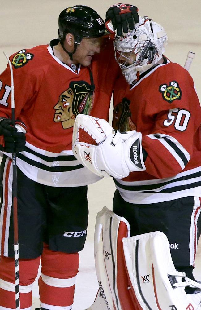 Chicago Blackhawks goalie Corey Crawford, right, celebrates with Marian Hossa after the Blackhawks defeated the Anaheim Ducks 4-2 in an NHL hockey game in Chicago, Friday, Jan. 17, 2014