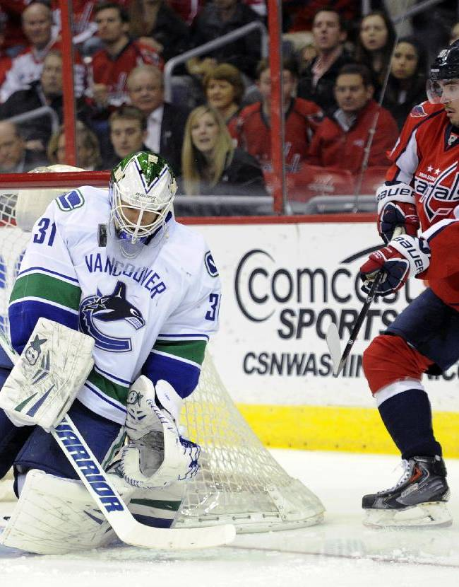 Vancouver Canucks goalie Eddie Lack (31) stops the puck as Washington Capitals center Marcus Johansson (90), of Sweden, watches during the first period of an NHL hockey game, Friday, March 14, 2014, in Washington