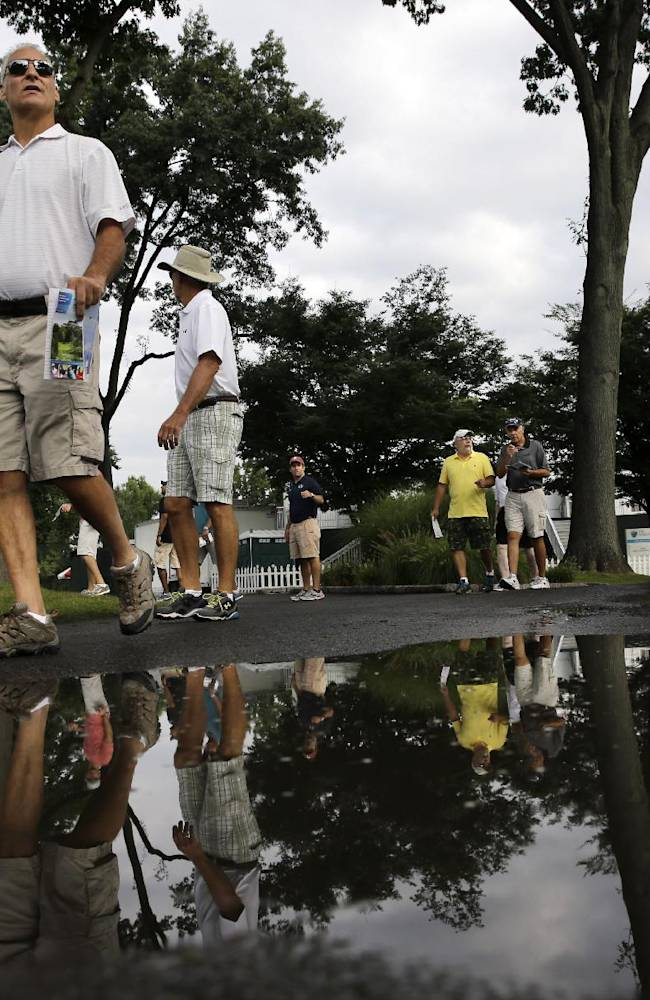 Spectators make their way after an overnight rain left puddles for the first round of play at The Barclays golf tournament Thursday, Aug. 21, 2014, in Paramus, N.J