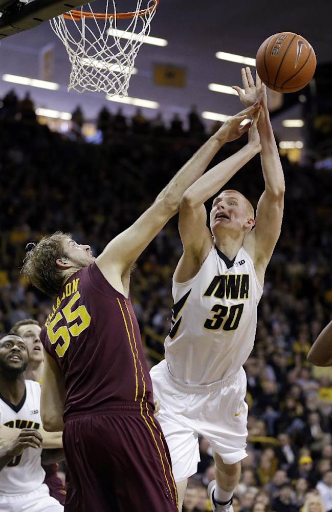 Iowa forward Aaron White, right, is fouled by Minnesota center Elliott Eliason (55) while driving to the basket during the second half of an NCAA women's college basketball game, Sunday, Jan. 19, 2014, in Iowa City, Iowa. White scored 18 points as Iowa won 94-73