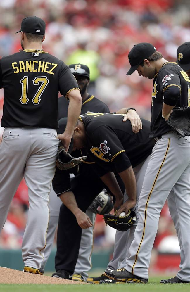Pittsburgh Pirates starting pitcher Francisco Liriano bends over as teammates gather around him during the third inning of a baseball game against the St. Louis Cardinals on Saturday, April 26, 2014, in St. Louis. Liriano left the game soon after