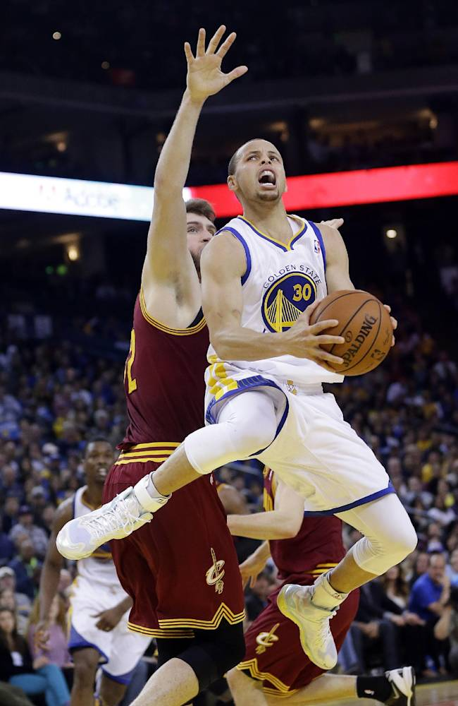 Golden State Warriors guard Stephen Curry, right, drives to the basket next to Cleveland Cavaliers center Spencer Hawes during the second half of an NBA basketball game Friday, March 14, 2014, in Oakland, Calif. Cleveland won 103-94