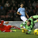 Manchester City's Sergio Aguero, center, watches as his unsuccessful attempt on goal passes Southampton's Jose Fonte, left, and goalkeeper Costel Pantilimon during the English Premier League soccer match between Southampton and Manchester City at St Mary'