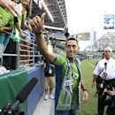 Clint Dempsey, captain of the United States Men's National Soccer Team, greets fans after he was introduced as the newest member of the team, Saturday, Aug. 3, 2013, prior to a MLS soccer match between the Sounders and FC Dallas in Seattle. Dempsey previously played for Tottenham Hotspur in the English Premier League. (AP Photo/Ted S. Warren)