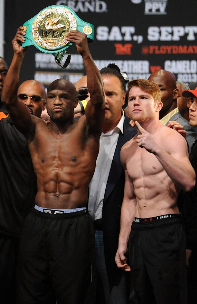 In this photo provided by the Las Vegas News Bureau, Floyd Mayweather Jr., left, and Canelo Alvarez pose after the weigh-in for the Saturday boxing bout, Friday, Sept. 13, 2013, in Las Vegas. Mayweather's WBA super world and Alvarez's WBC junior middleweight titles are on the line