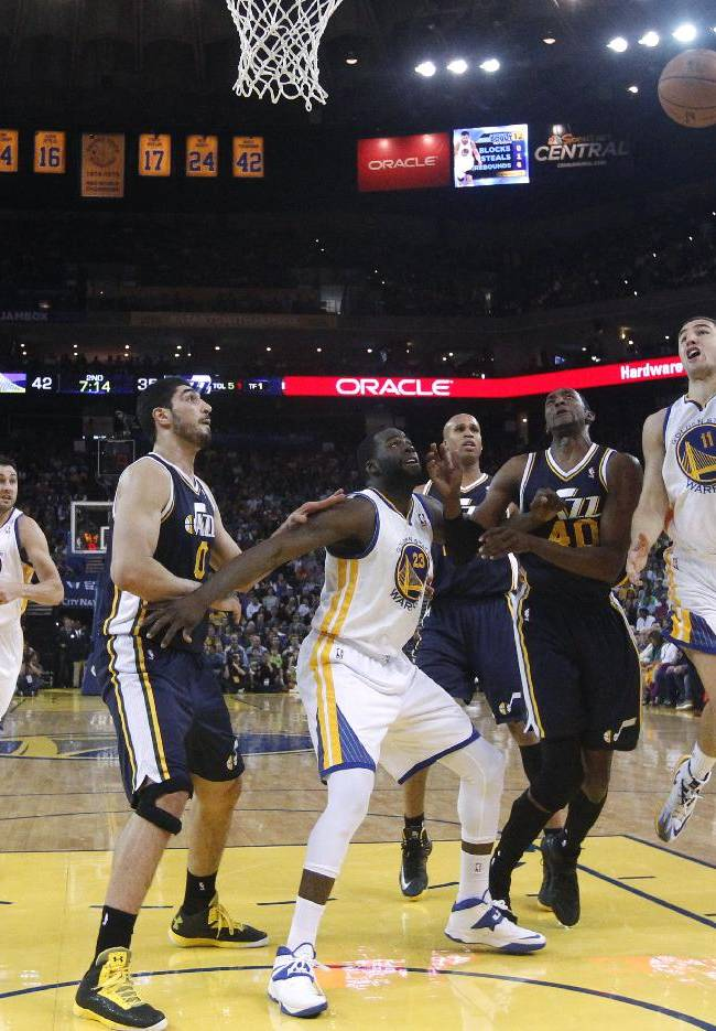 Golden State Warriors guard Klay Thompson, right, goes up for a shot against the Utah Jazz during the first half of an NBA basketball game Sunday, April 6, 2014, in Oakland, Calif