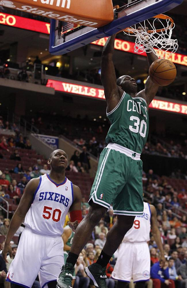 Boston Celtics' Brandon Bass, right, dunks the ball as Philadelphia 76ers' Lavoy Allen, left, looks on during the first half of an NBA basketball game, Wednesday, Feb. 5, 2014, in Philadelphia