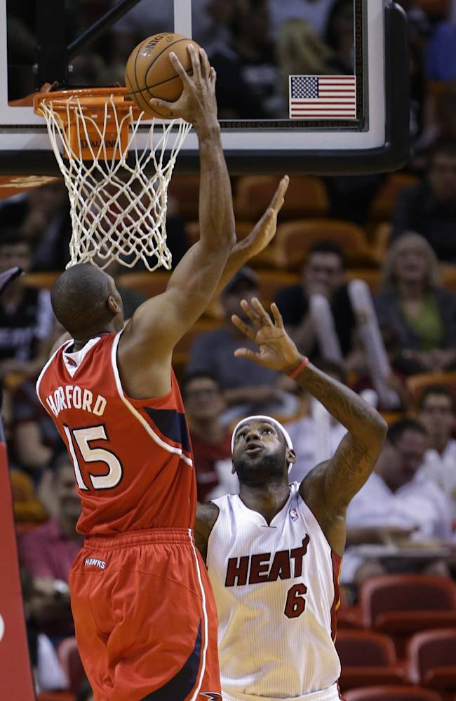 Atlanta Hawks center Al Horford (15) of the Dominican Republic, goes up for a shot against Miami Heat forward LeBron James (6) during the first half of an NBA basketball game, Tuesday, Nov. 19, 2013 in Miami
