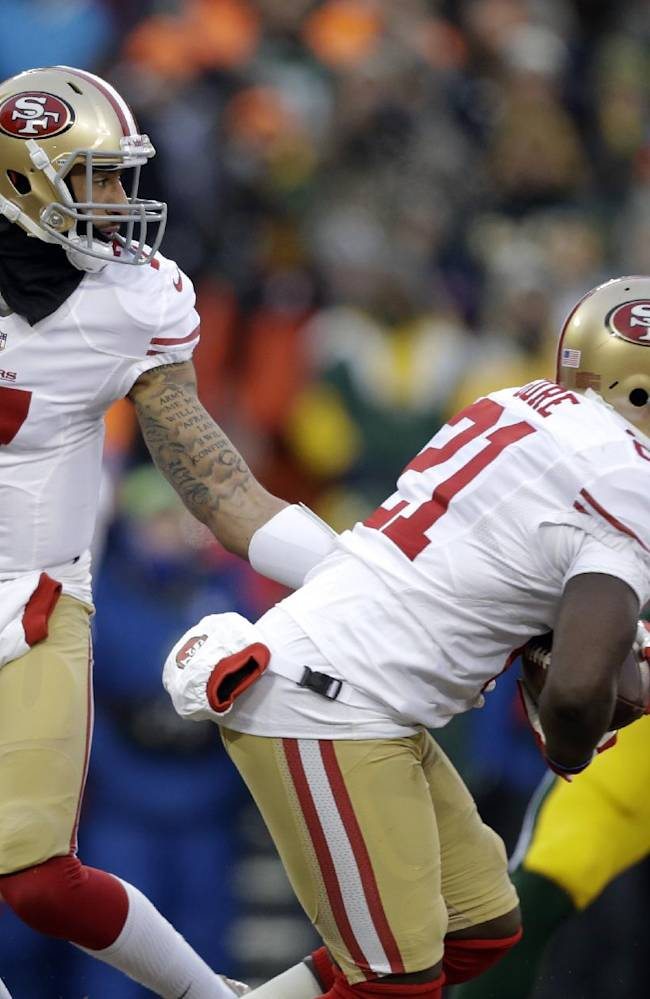 San Francisco 49ers quarterback Colin Kaepernick (7) hands off the ball to running back Frank Gore (21) during the first half of an NFL wild-card playoff football game against the Green Bay Packers, Sunday, Jan. 5, 2014, in Green Bay, Wis