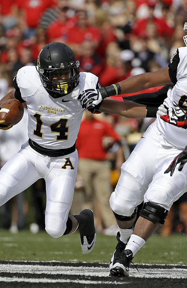 Appalachian State's Marcus Cox, left, runs the ball against the defense of Georgia's Amarlo Herrera, right, in the first quarter of an NCAA college football game, Saturday, Nov. 9, 2013, in Athens, Ga