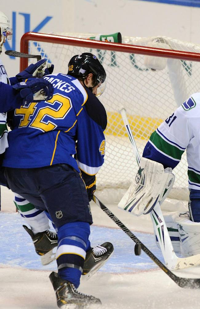 Vancouver Canucks' goalie Eddie Lack (31), of Sweden, blocks a shot by St. Louis Blues' David Backes (42) as Canucks' Ryan Stanton (18) defends during the second period of an NHL hockey game on Friday, Oct. 25, 2013, in St. Louis