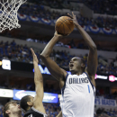 Dallas Mavericks center Samuel Dalembert (1) shoots over San Antonio Spurs guard Danny Green (4) and Tiago Splitter during the first half in Game 3 in the first round of the NBA basketball playoffs in Dallas, Saturday, April 26, 2014. (AP Photo/LM Otero)