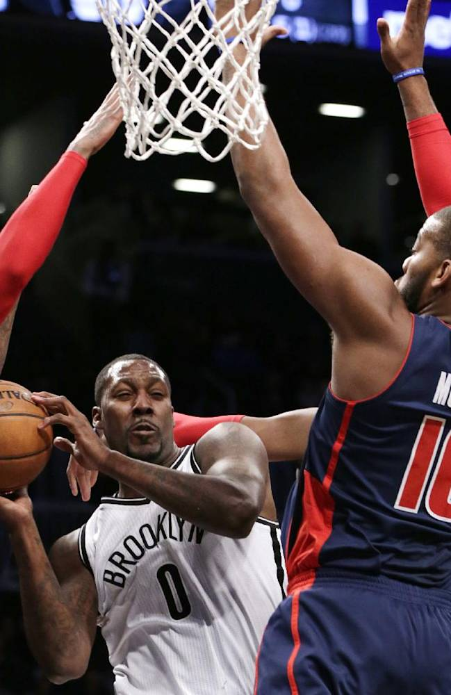 Brooklyn Nets center Andray Blatche (0) looks to pass as Detroit Pistons forward Greg Monroe (10) tries to block him in the first half of an NBA basketball game, Sunday, Nov. 24, 2013, in New York