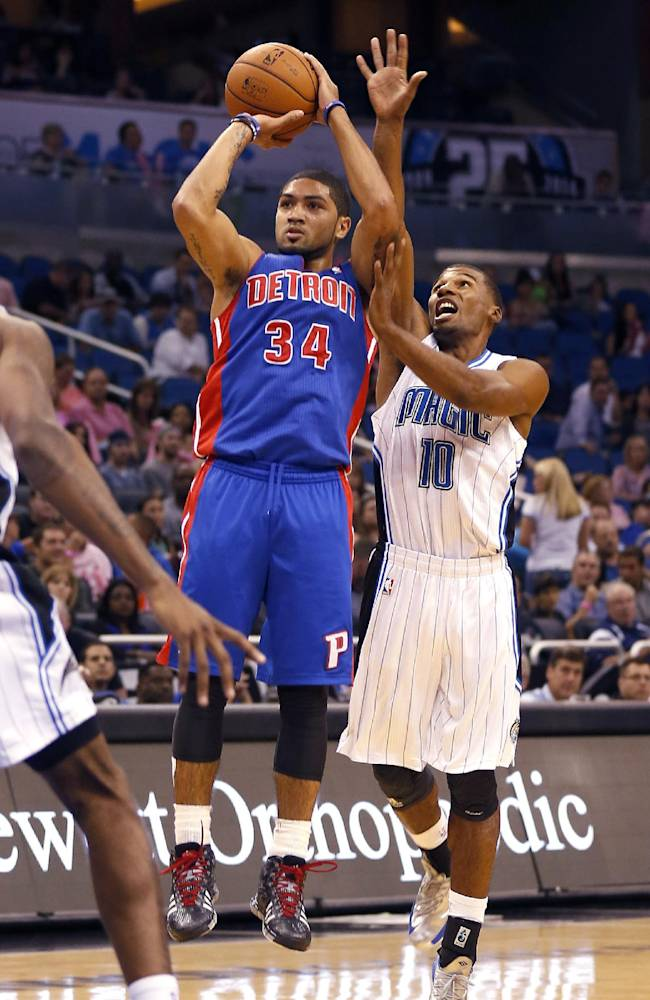 Detroit Pistons guard Peyton Siva (34) gets fouled while shooting in front of Orlando Magic point guard Ronnie Price (10) during the first half of an NBA basketball game on Sunday,  Oct.  20, 2013 in Orlando, Fla