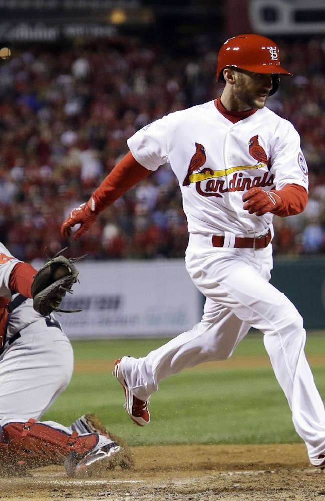 St. Louis Cardinals' Shane Robinson scores past Boston Red Sox catcher David Ross during the seventh inning of Game 4 of baseball's World Series Sunday, Oct. 27, 2013, in St. Louis. Robinson scored from second on a hit by Matt Carpenter