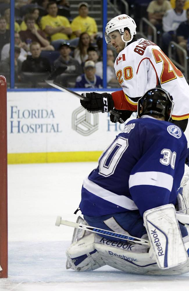 Calgary Flames left wing Curtis Glencross (20) slips the puck past Tampa Bay Lightning goalie Ben Bishop (30) for a goal during the third period of an NHL hockey game on Thursday, April 3, 2014, in Tampa, Fla. Lightning's Valtteri Filppula (51), of Finland, also defends. The Flames won the game 4-1