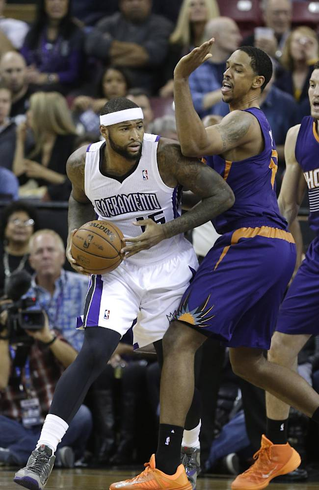 Sacramento Kings center DeMarcus Cousins, left, looks to pass against Phoenix Suns center Channing Frye during the first quarter of an NBA basketball game in Sacramento, Calif., Tuesday, Nov. 19, 2013