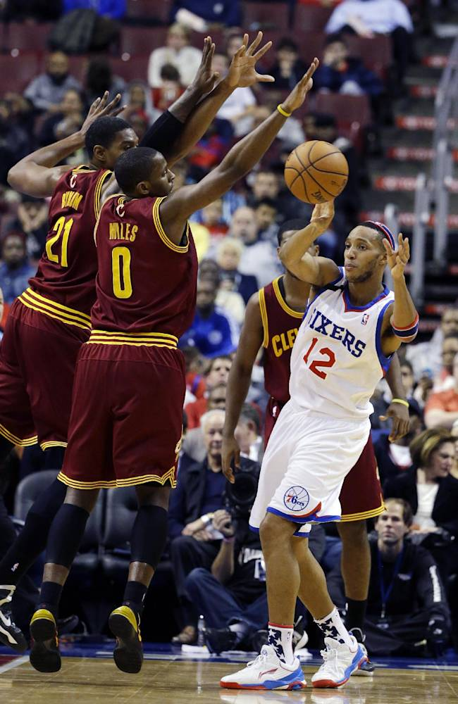 Philadelphia 76ers' Evan Turner (12) passes the ball under pressure from Cleveland Cavaliers' C.J. Miles (0) and Andrew Bynum (21) during the first half of an NBA basketball game, Friday, Nov. 8, 2013, in Philadelphia