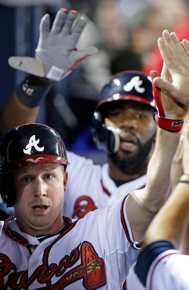 Atlanta Braves' Elliot Johnson, left, and Jason Heyward, rear right, high-five teammates after scoring off a double by Evan Gattis in the second inning of a baseball game against the Philadelphia Phillies, Thursday, Sept. 26, 2013, in Atlanta