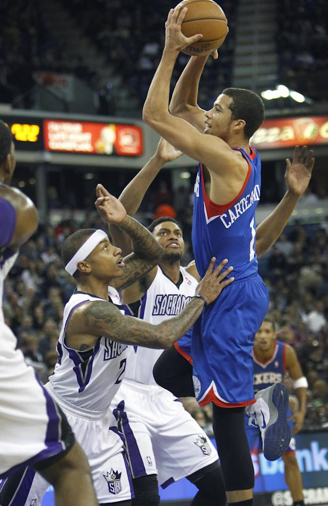 Philadelphia 76ers guard Michael Carter-Williams, right, shoots over Sacramento Kings defenders Isaiah Thomas (22) and Rudy Gay (8) during the first half of an NBA basketball game in Sacramento, Calif., on Thursday, Jan. 2, 2014