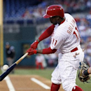 CORRECTS THAT RBI SCORED TONY GWYNN JR. NOT MARLON BYRD. - Philadelphia Phillies' Jimmy Rollins connects for an RBI-single, scoring Tony Gwynn Jr. from second base during the first inning of a baseball game against the Miami Marlins, Saturday, April 12, 2