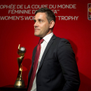 Canadian national women's soccer team head coach John Herdman stands next to the championship trophy following a FIFA Women's World Cup soccer news conference Friday, Dec. 5, 2014 in Ottawa. Teams will find out their first-round groups Saturday at the Women's World Cup draw. The tournament begins next summer in Canada. (AP Photo/The Canadian Press, Adrian Wyld)