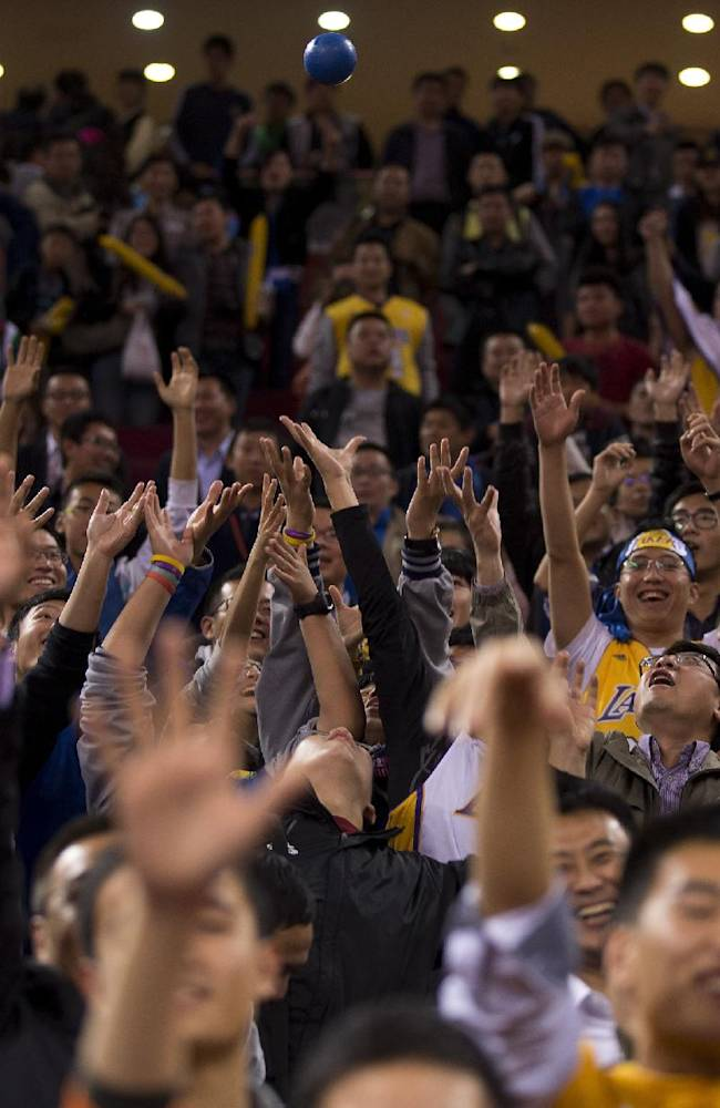 Chinese fans try to grab a ball thrown by LA Lakers and Golden State Warriors players after the NBA Global Game at the Wukesong Stadium in Beijing, Tuesday, Oct. 15, 2013. The Warriors defeated Lakers 100-95