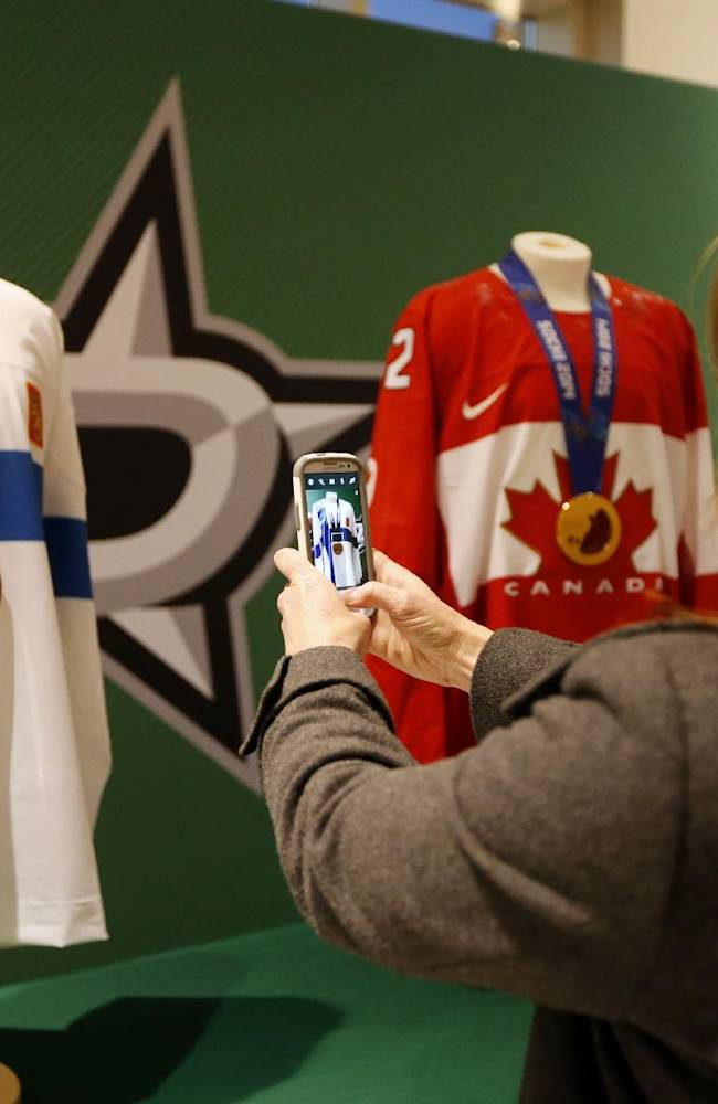 Dallas Stars fans take photos of medals won at the recent Winter Olympics by Stars goalie Kari Lehtonen, of Finland and center Jamie Benn before an NHL hockey game against the Carolina Hurricanes, Thursday, Feb. 27, 2014, in Dallas