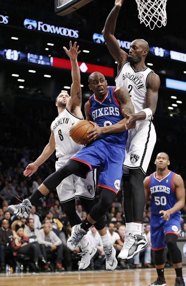 Brooklyn Nets guard Deron Williams (8) and Nets forward Kevin Garnett (2) defend Philadelphia 76ers guard James Anderson (9) in the second half of their NBA basketball game at the Barclays Center, Monday, Feb. 3, 2014 in New York. The Nets defeated the Sixers 108-102