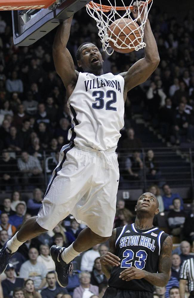 Villanova's James Bell (32) dunks as Seton Hall's Fuquan Edwin (23) watches during the second half of an NCAA college basketball game, Friday, Feb. 7, 2014, in Villanova, Pa. Villanova won 70-53