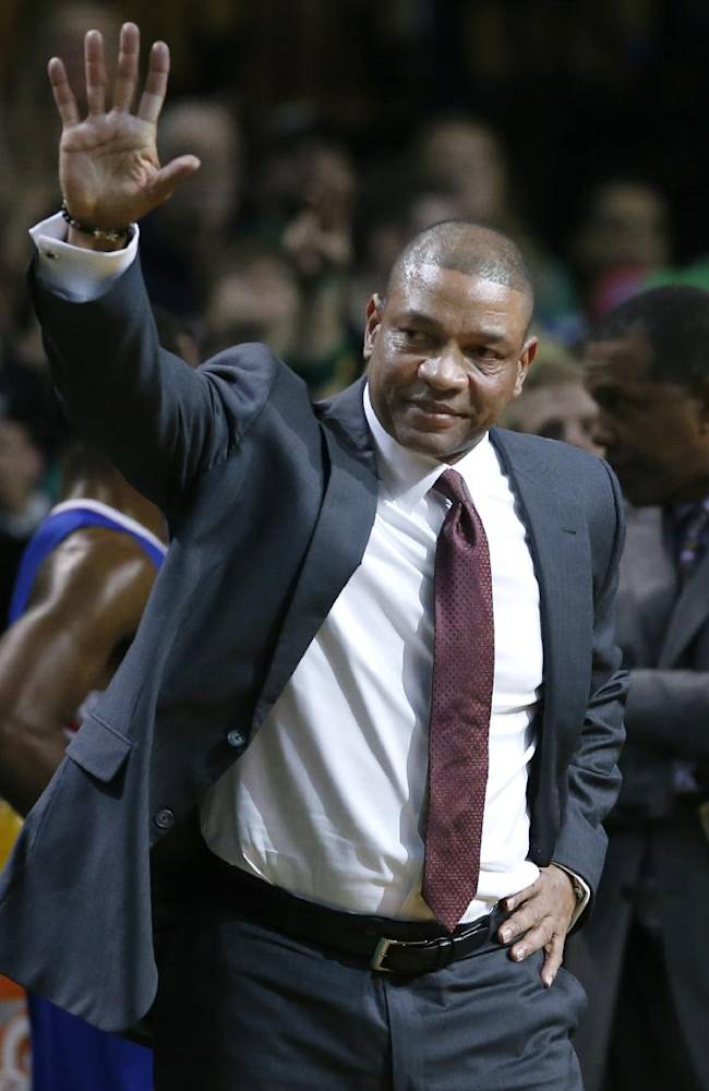 Current Los Angeles Clippers head coach and former Boston Celtics head coach Doc Rivers waves during a video tribute to him for his first time back to the TD Garden, after the first quarter of an NBA basketball game in Boston, Wednesday, Dec. 11, 2013