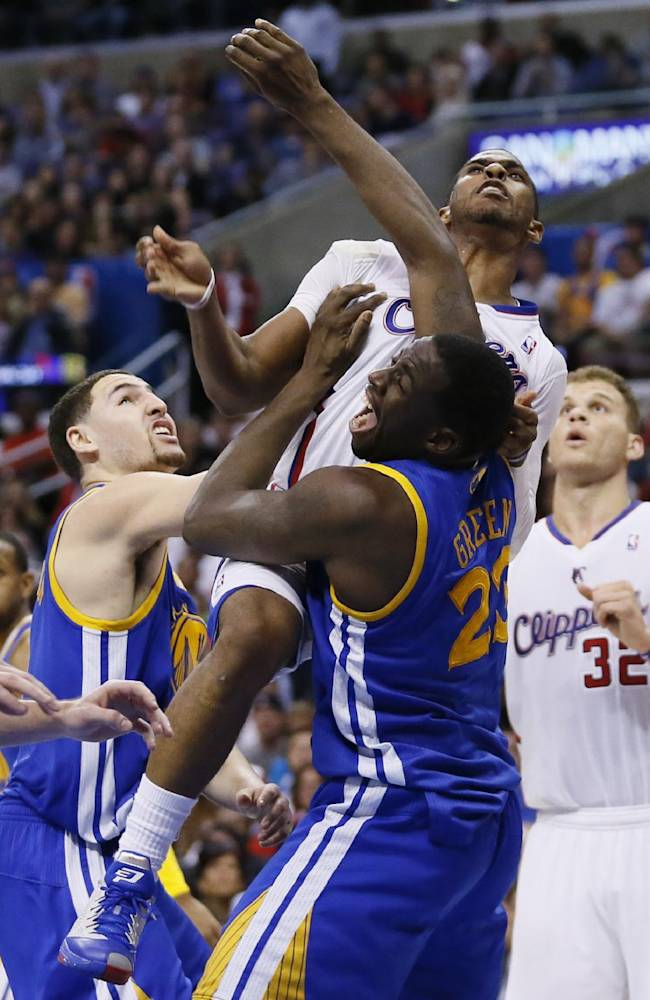 Los Angeles Clippers' Chris Paul collides with Golden State Warriors' Draymond Green, right, as Klay Thompson, left, also defends during the second half of an NBA basketball game in Los Angeles, Wednesday, March 12, 2014. The Clippers won 111-98