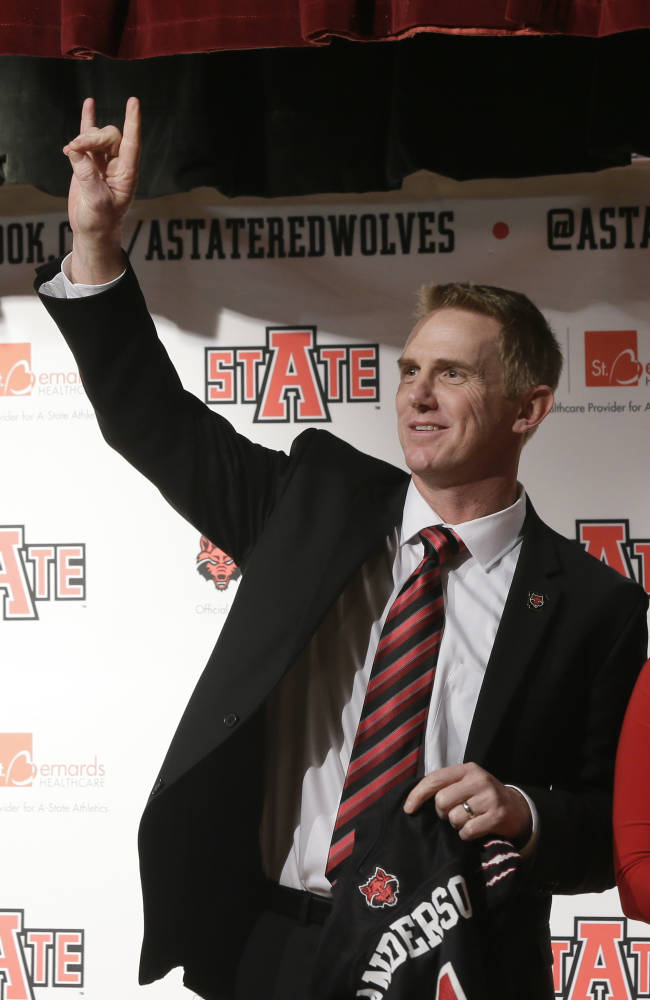 Former North Carolina offensive coordinator Blake Anderson waves after being named head football coach at Arkansas State in Jonesboro, Ark., Thursday, Dec. 19, 2013