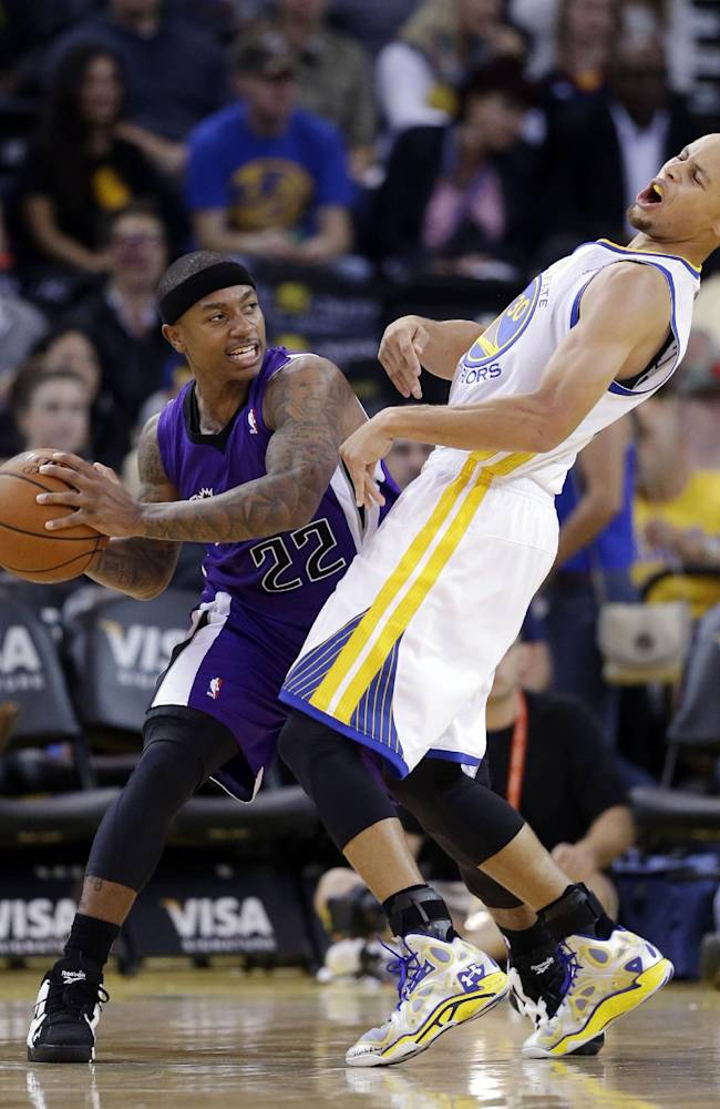 Sacramento Kings' Isaiah Thomas, left, tries to move the ball against Golden State Warriors' Stephen Curry during the second half of an NBA preseason basketball game Monday, Oct. 7, 2013, in Oakland, Calif