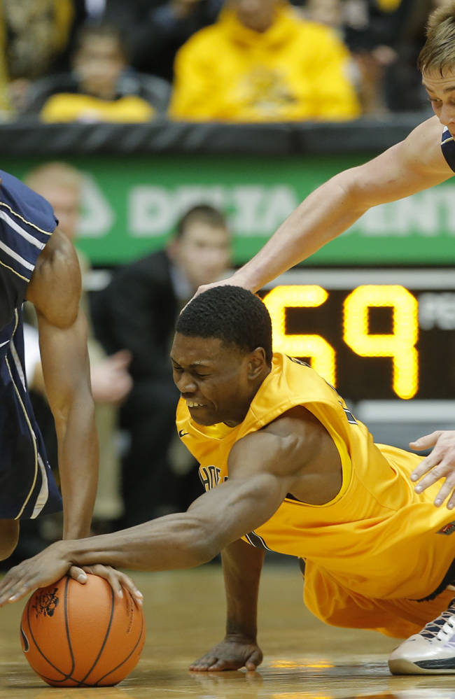 Wichita State's Cleanthony Early dives for a loose ball against Oral Roberts' Bobby Word, left, and Jorden Kaufman, right, during the first half of their game in Wichita, Kan. on Saturday, Dec. 7, 2013