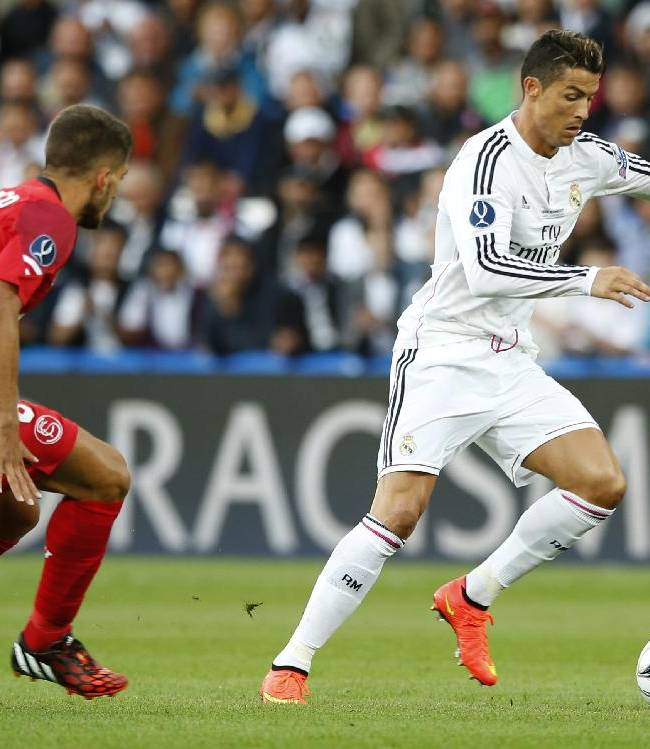 Real Madrid's Cristiano Ronaldo in action with Sevilla's Daniel Carrico during the UEFA Super Cup soccer match between Real Madrid and Sevilla in Cardiff City Stadium, in Cardiff, Wales, Tuesday, Aug. 12, 2014
