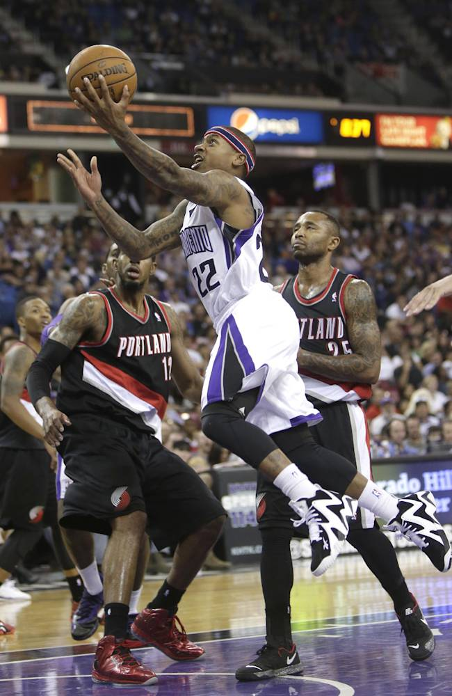 Sacramento Kings guard Isaiah Thomas, center, goes to the basket against Portland Trail Blazers' LaMarcus Aldridge, left, and Mo Williams, right, during the third quarter of an NBA basketball game in Sacramento, Calif., Saturday, Nov. 9, 2013.  The Trail Blazers won 96-85