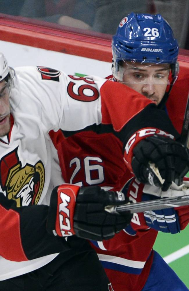 Ottawa Senators' Mike Hoffman, left, checks Montreal Canadiens' Josh Georges during the first period of an NHL preseason game, Thursday, Sept. 26, 2013 in Montreal