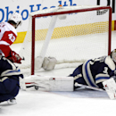Columbus Blue Jackets goalie Curtis McElhinney (31) stops a shot against Detroit Red Wings' Darren Helm (43) as Blue Jackets' Matt Calvert (11) collides with Helm in the third period of an NHL hockey game in Columbus, Ohio, Tuesday, March 25, 2014 The As