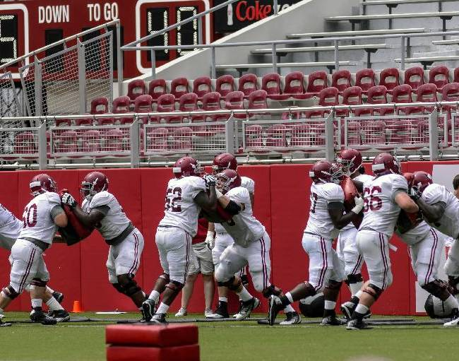 Alabama's offensive line works through drills at football practice, Saturday, Aug. 9, 2014, at Bryant-Denny Stadium in Tuscaloosa, Ala