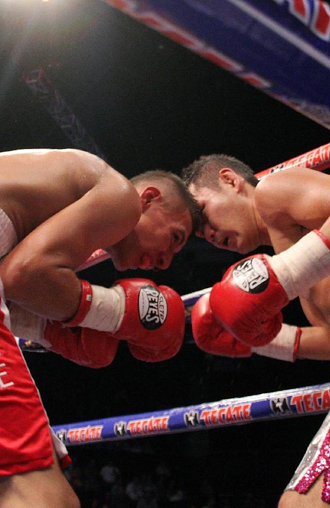 Mexico's Francisco Rodriguez, left, exchanges a punch with Japan's Katsunari Takayama, during their  IBF and WBO minimumweight title unification  in Monterrey, Mexico, Saturday Aug. 9, 2014