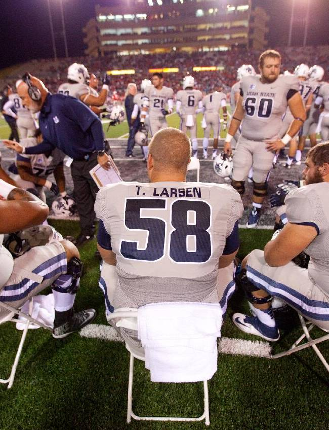 Utah State center Tyler Larsen, center, sits with his team on the sidelines during the first half of an NCAA college football game against New Mexico, Saturday, Oct. 19, 2013 in Albuquerque, N.M. Utah State won 45-10
