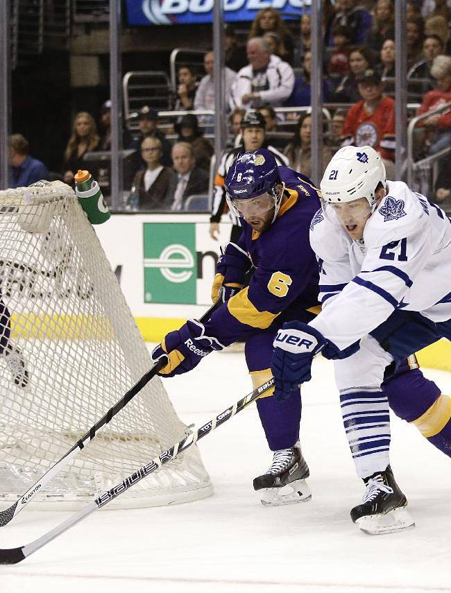 Los Angeles Kings' Jake Muzzin (6) defends Toronto Maple Leafs' James van Riemsdyk (21) as Kings goalie Jonathan Quick (32) watches during the first period of an NHL hockey game on Thursday, March 13, 2014, in Los Angeles