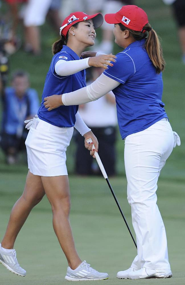 So Yeon Ryu, left, and Inbee Park, both of South Korea, celebrate sinking winning the playoff hole against the United States in the International Crown golf tournament Saturday, July 26, 2014, in Owings Mills, Md