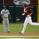 Arizona Diamondbacks' Mark Trumbo, right, runs past Los Angeles Dodgers third baseman Juan Uribe after hitting a three-run home run during the seventh inning of a baseball game on Sunday, April 13, 2014, in Phoenix The Associated Press